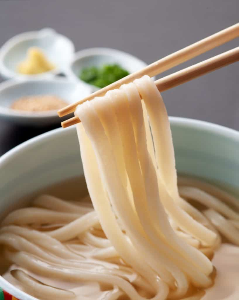 cooked udon noodles being held in chopsticks over bowl of soup