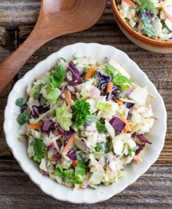 white scalloped bowl filled with vegan coleslaw on rustic wooden table with wooden spoon