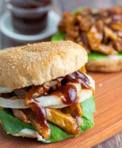 vegan seitan bbq sandwich on bun with bbq sauce in background