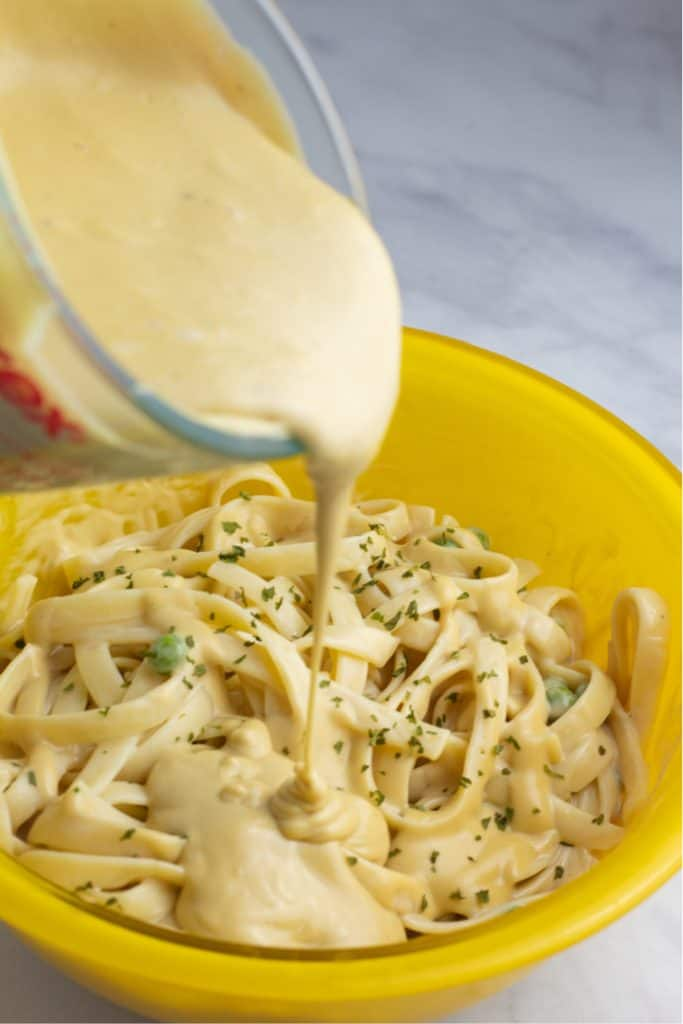 vegan alfredo sauce being poured over pasta in large yellow bowl