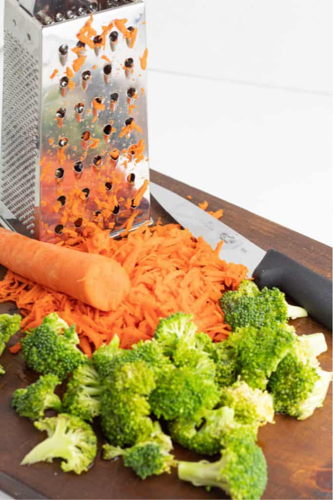 grated carrots with grater on wooden cutting board with broccoli