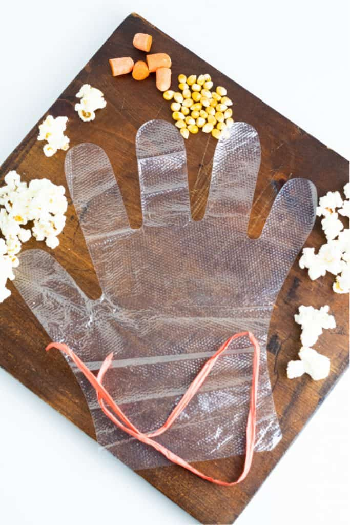 clear glove with popcorn kernels on wood board