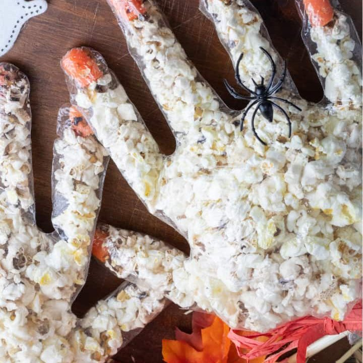 halloween popcorn hands with spider ring on one finger overhead shot