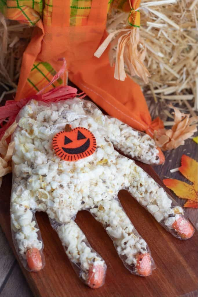 clear glove stuffed with popcorn with small pumpkin on outside