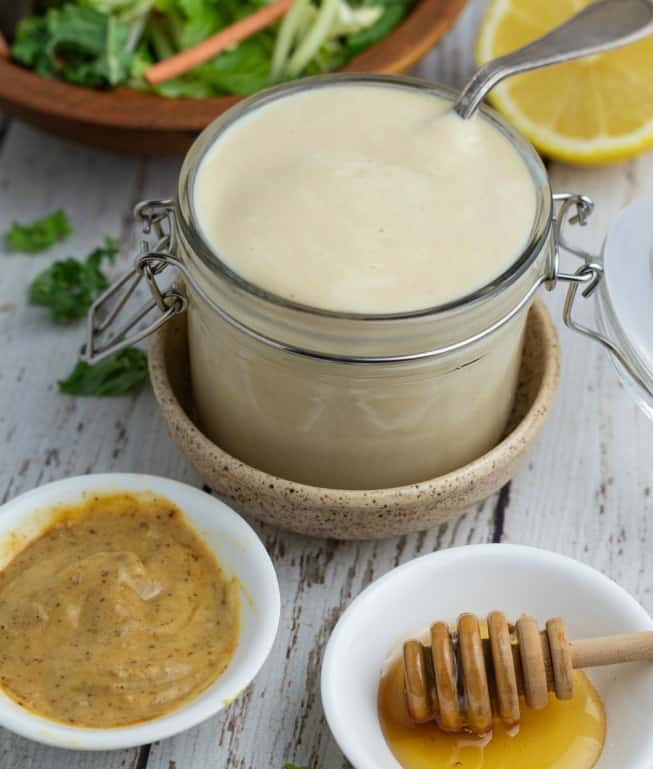 jar filled with honey mustard dressing with small white bowls of dijon mustard and honey setting in front