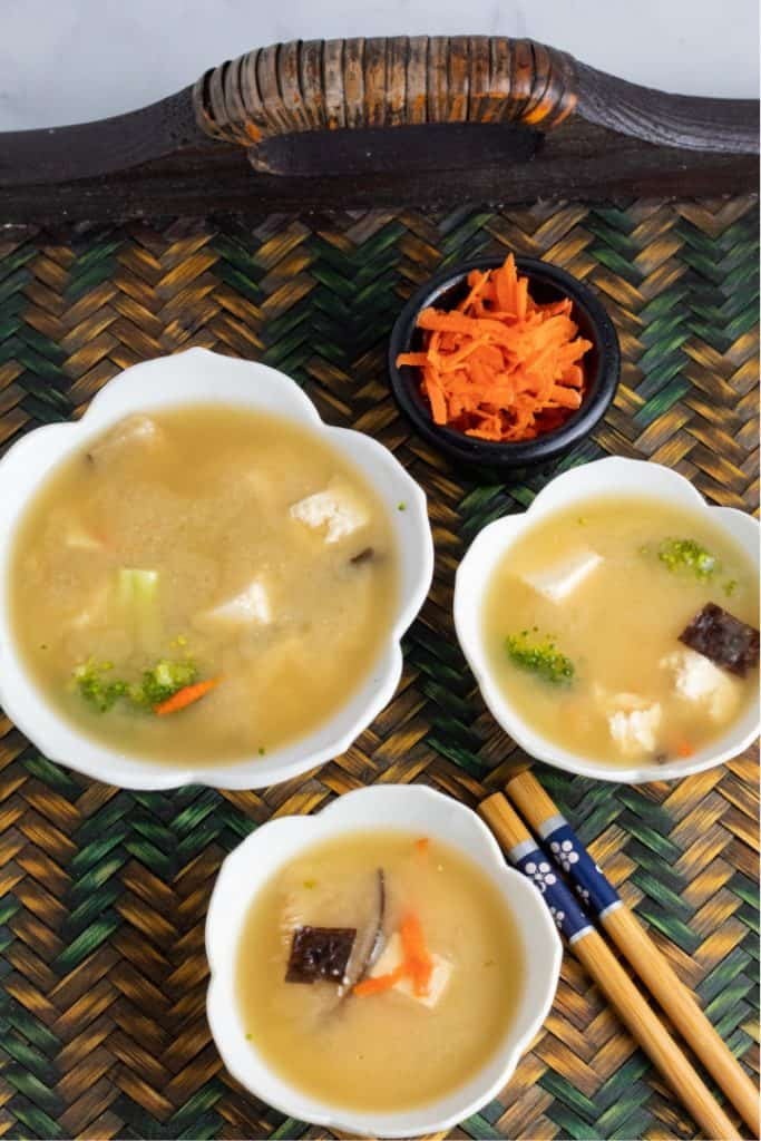 Overhead photo of 3 white bowls of miso soup with chopsticks