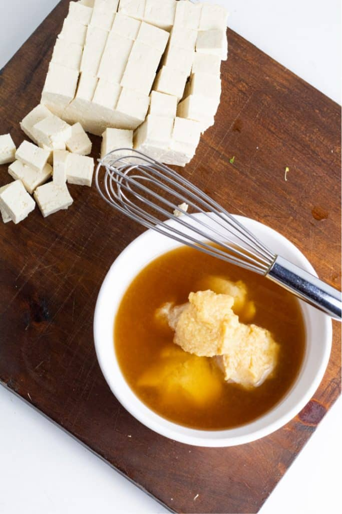miso in veggie broth in bowl with whisk on cutting board with diced tofu