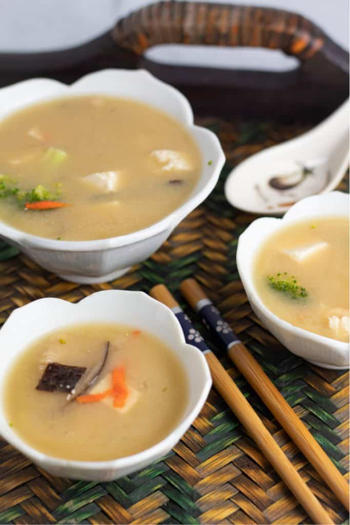 3 white bowls of miso soup with chopsticks