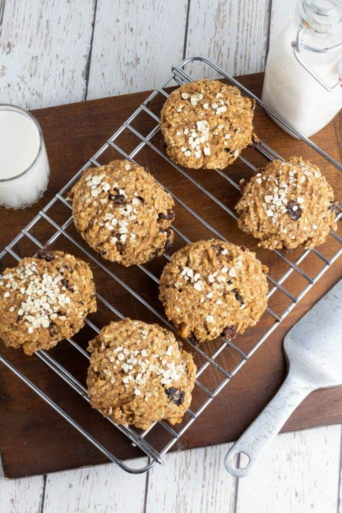 6 oatmeal vegan cookies on cooking rack with glass of almond milk