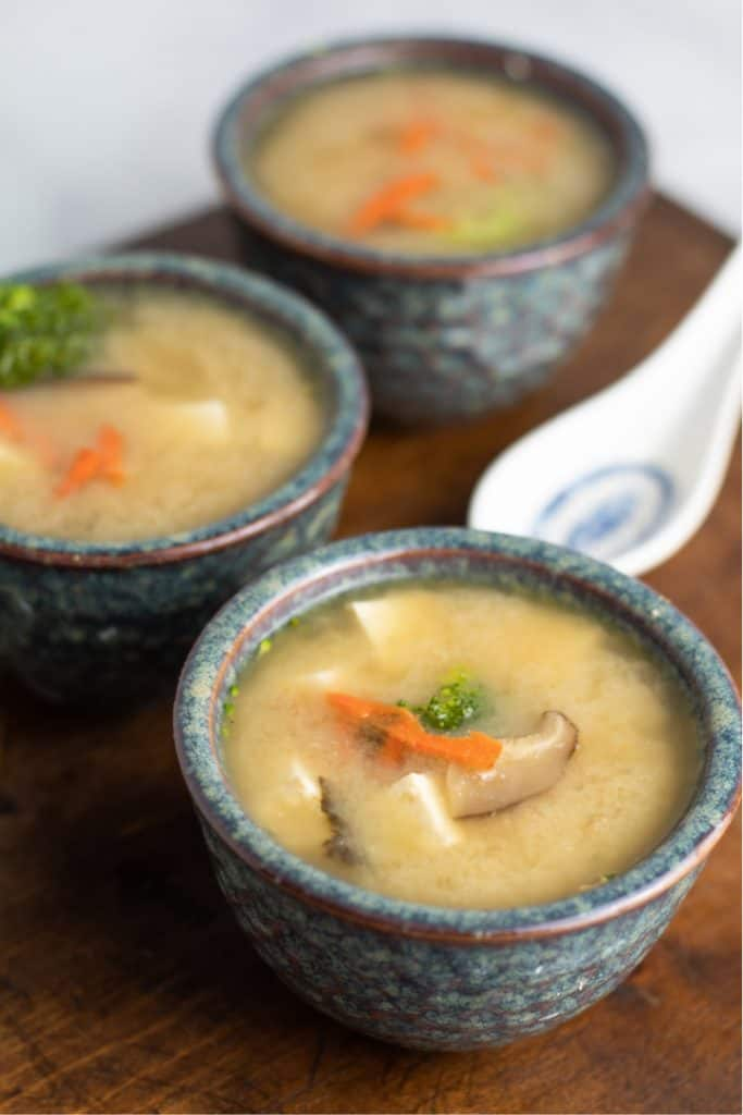 3 blue green bowls of miso soup on dark cutting board