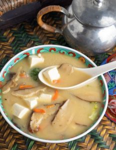 overhead photo of large bowl of miso soup with tofu and mushrooms with white asian soup spoon