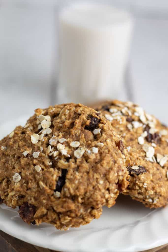 oatmeal raisin cookies on white plate with glass of almond milk in background