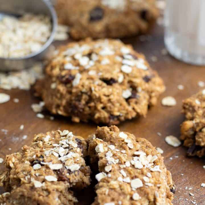 oatmeal cookie torn in half on wooden board with more cookies in background