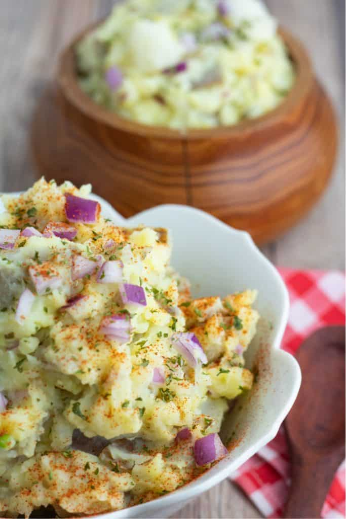 close up of vegan potato salad in white bowl