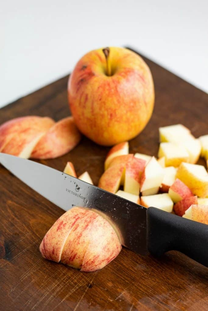 whole apple and diced apple on cutting board with knife