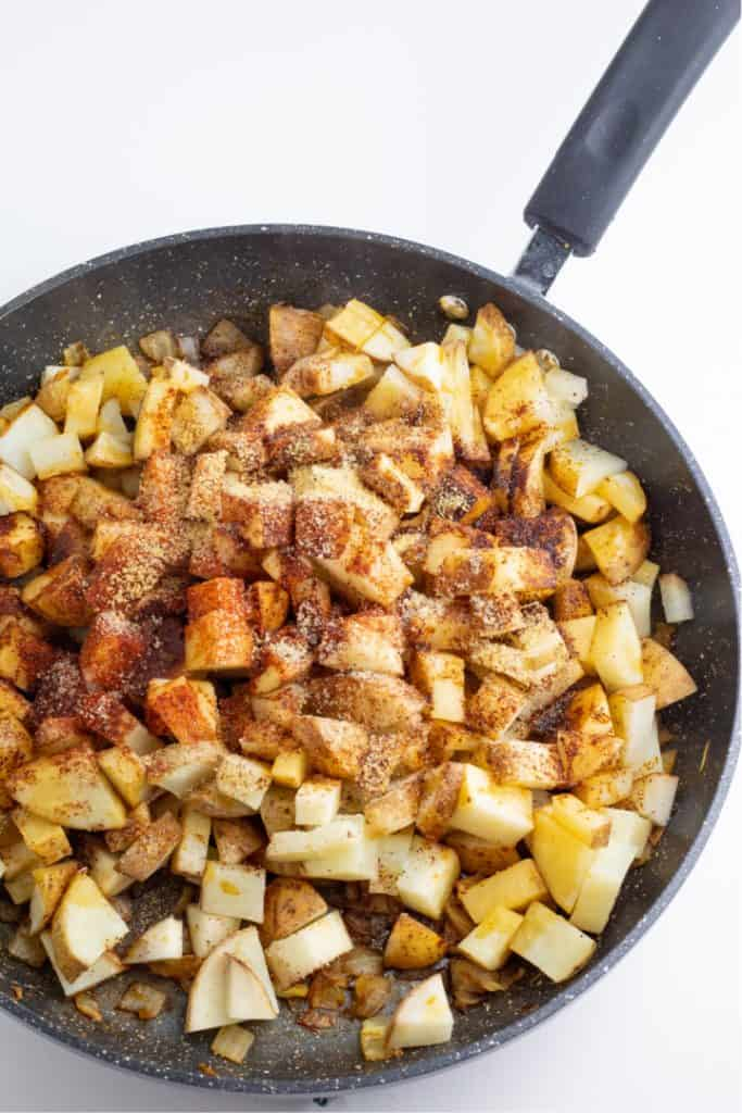 diced potatoes and onions in nonstick skillet