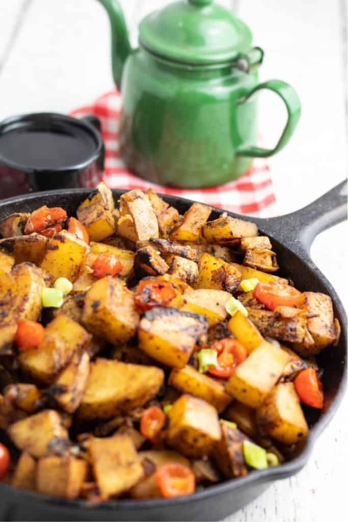 breakfast potatoes in cast iron skillet with old green coffee pot in background