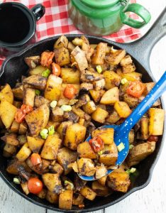 cooked breakfast potatoes in cast iron skillet with bright blue spoon