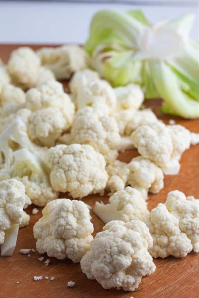 diced chunks of raw cauliflower on cutting board