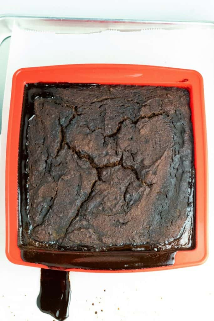 chocolate fudge cake in red baking pan dripping out