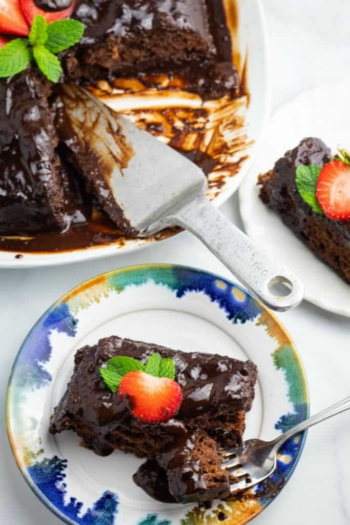 vegan fudge cake overhead of slice on plate and pan with serving utensil