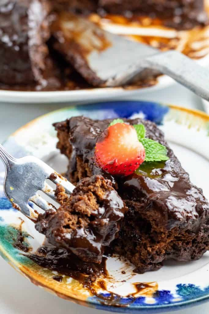 fork full of fudge cake next to plate with slice