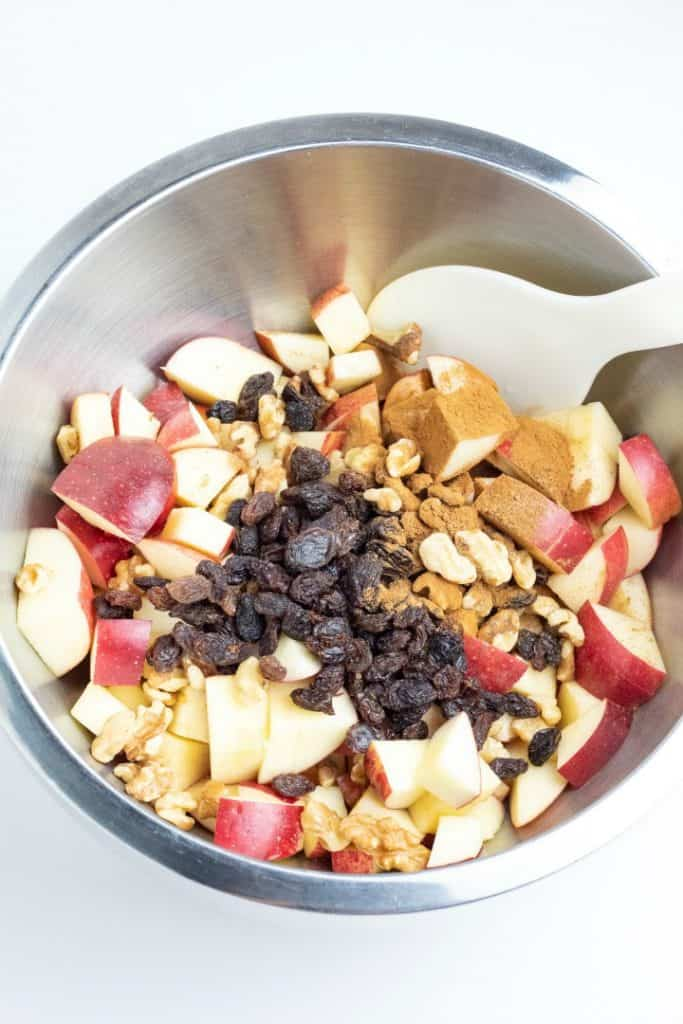 large stainless mixing bowl with diced apples, raisins, walnuts, and spices