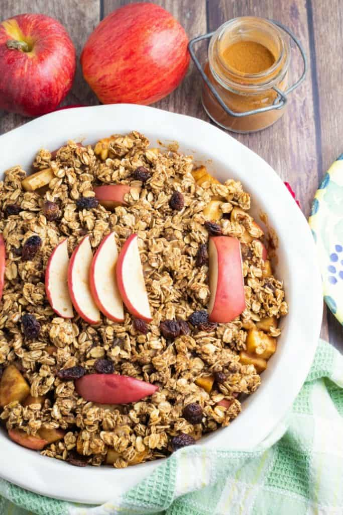 round baking glass pan with healthy apple crumble apples and cinnamon jar in background