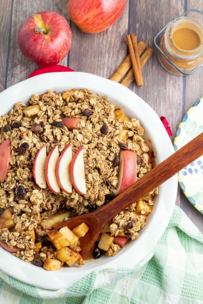 round baking glass pan with healthy apple crumble and wooden spoon and apples and cinnamon in background
