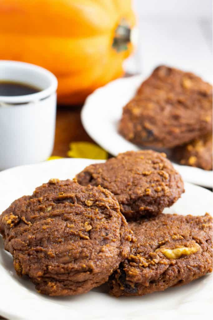 white plate with 3 pumpkin cookies and whole pumpkin in background