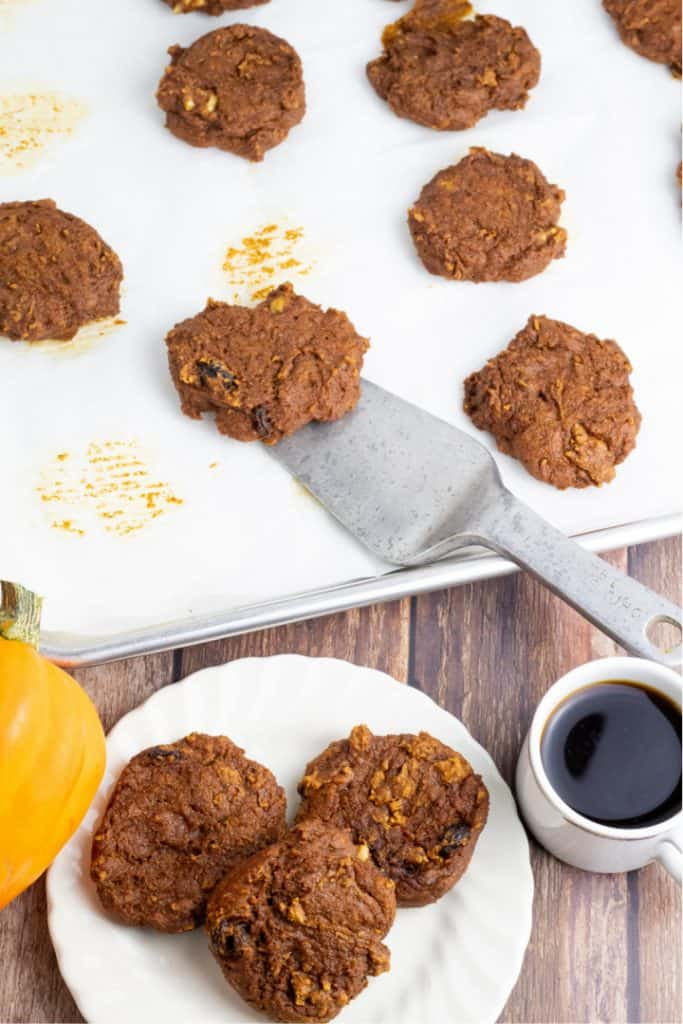 overhead photo of baking pan full of pumpkin cookies and white plate with 3 and cup of coffee