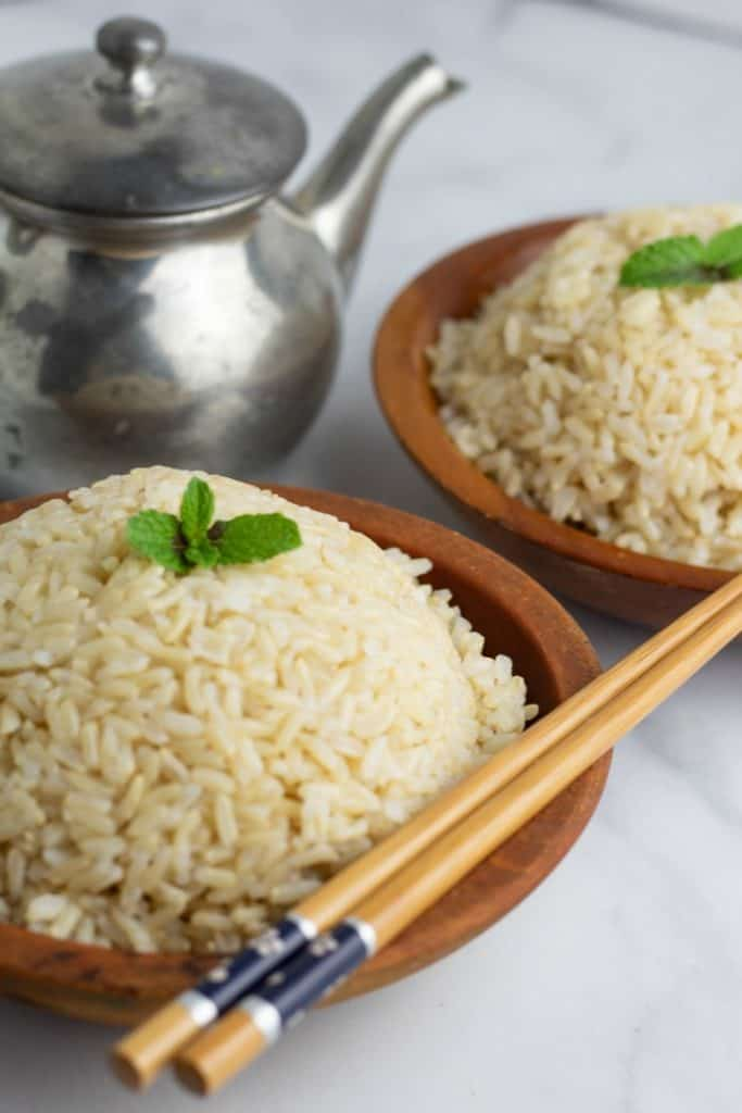cooked brown rice in wooden bowl with chopsticks teapot in background