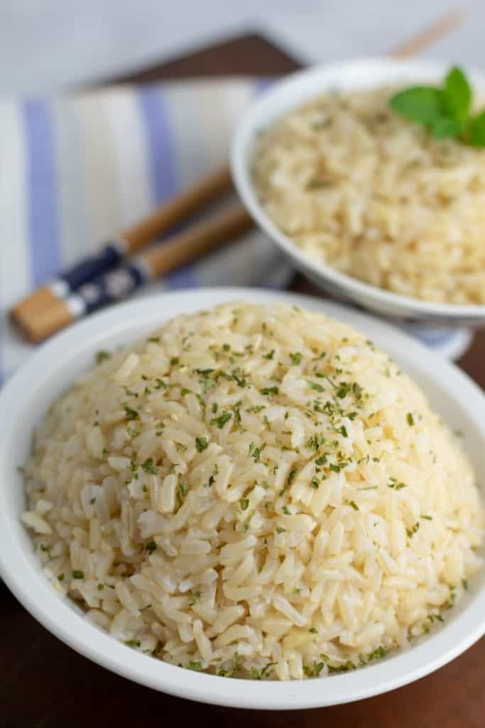 brown rice in white bowls with parsley sprinkled on top