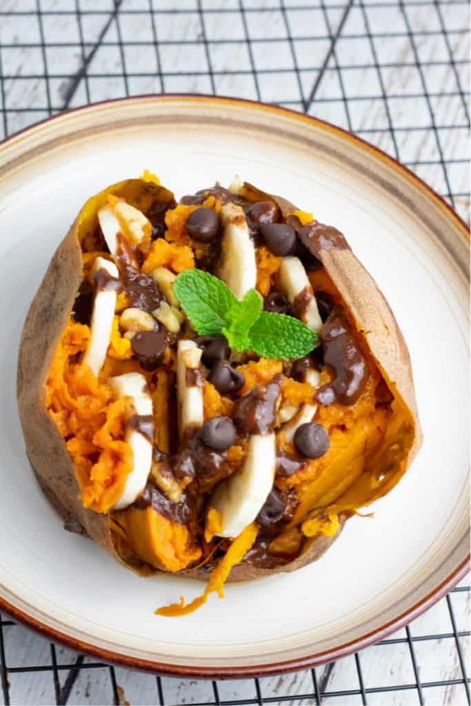 loaded sweet potato with banana slices and chocolate chips on white plate
