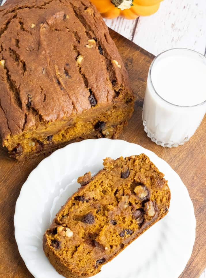 overhead photo of slice of pumpkin bread on white plate with glass of almond milk