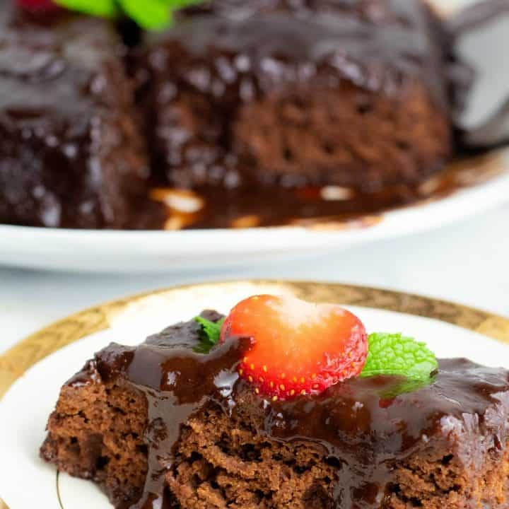 sice of chocolate cake on white plate topped with strawberry