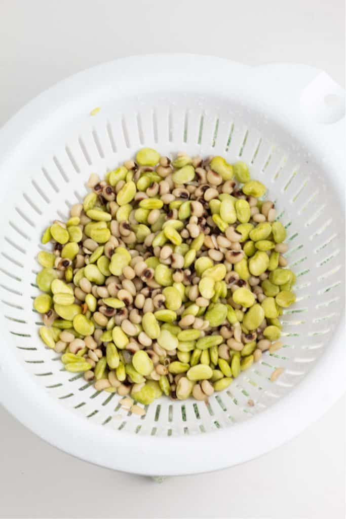 lima beans and black eyed peas in white colander