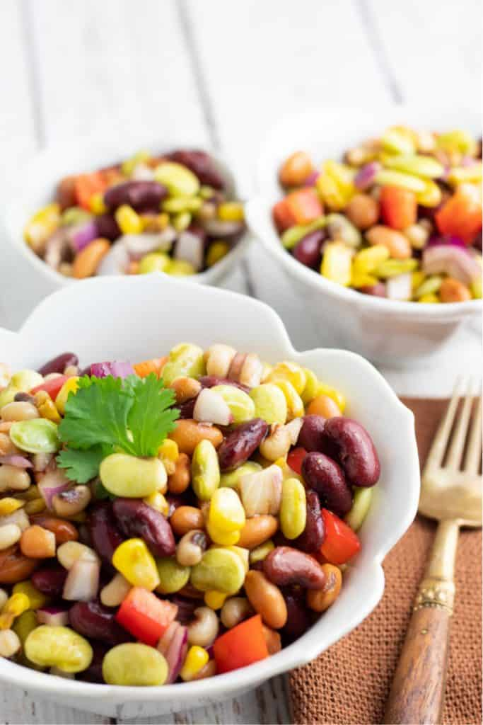 mixed bean salad topped with cilantro in white bowl
