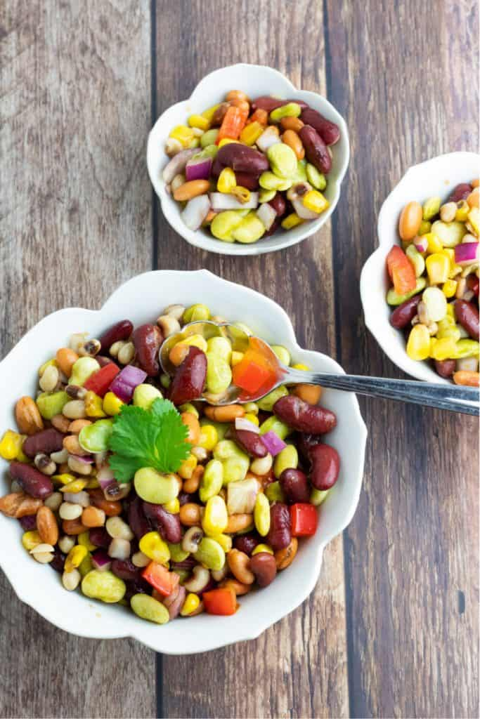 overhead of mixed bean salad in 3 white bowls