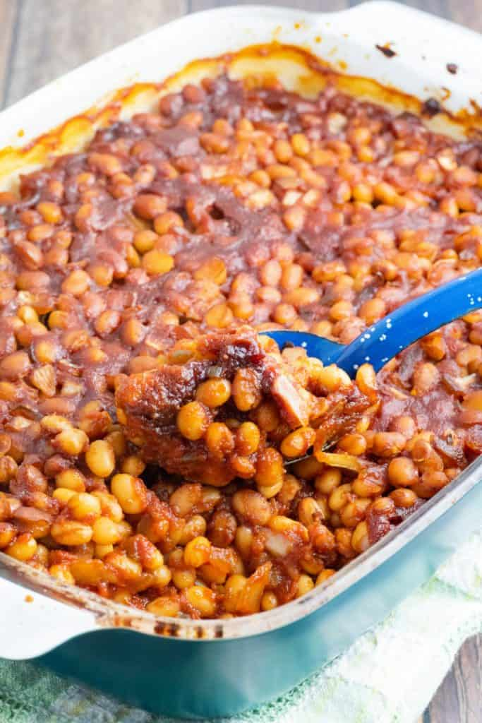 casserole dish full of vegan baked beans being scooped out with bright blue spoon