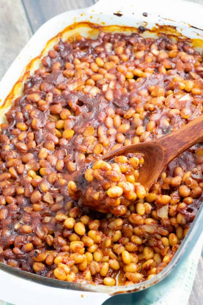 casserole dish of baked beans with wooden spoon