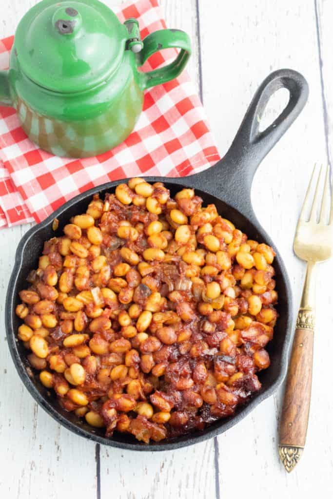 round cast iron pan of vegan baked beans with green old rustic teapot