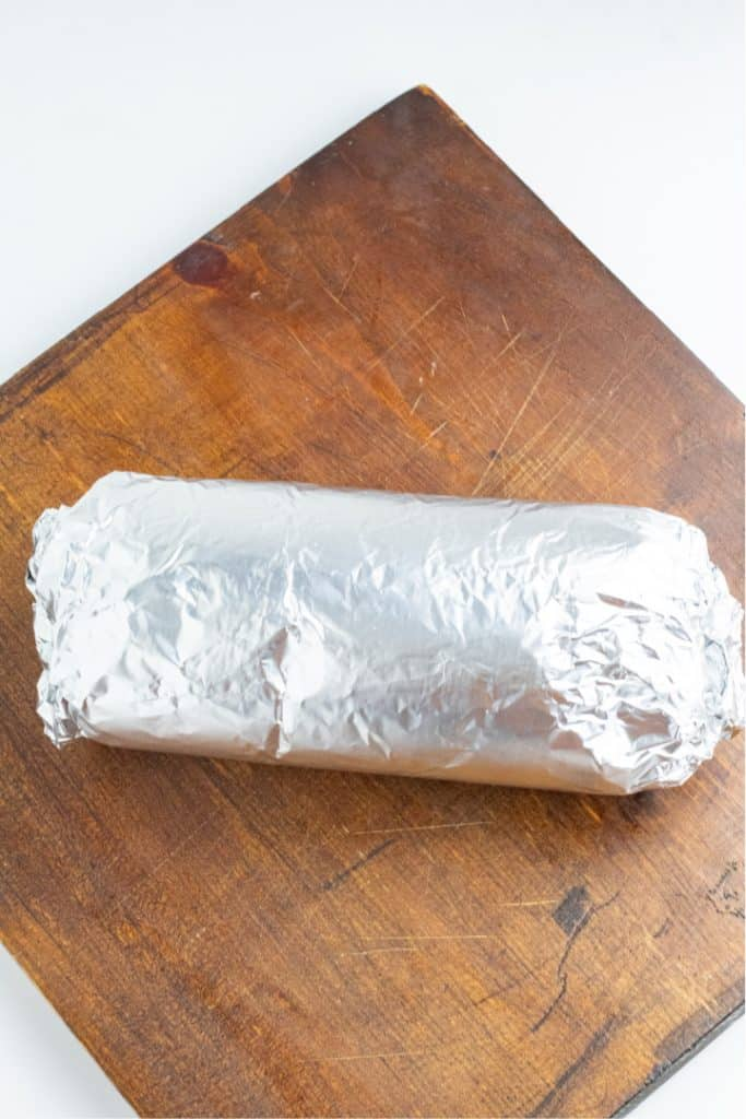 vegan roast wrapped in foil on cutting board