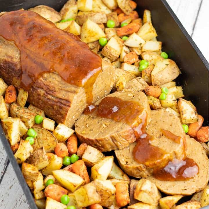 vegan roast with roasted potatoes and carrots in cast iron baking dish