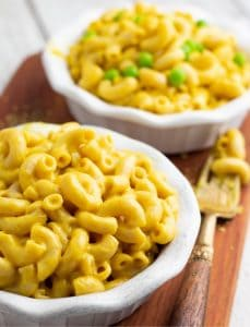 vegan mac and cheese in white bowls on wood board