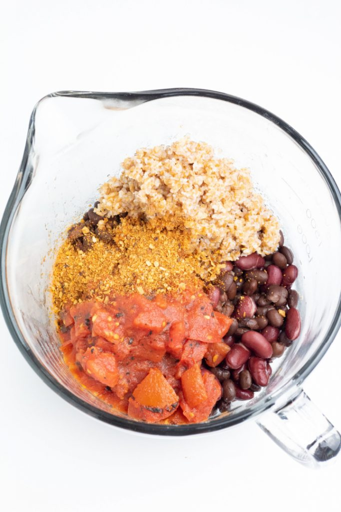 clear mixing bowl with beans, bulgur, salsa, taco seasoning