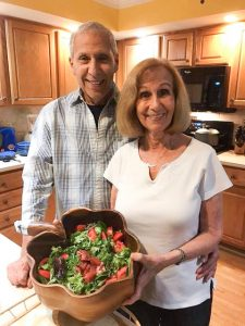 bob and fran german in kitchen holding bowl of salad