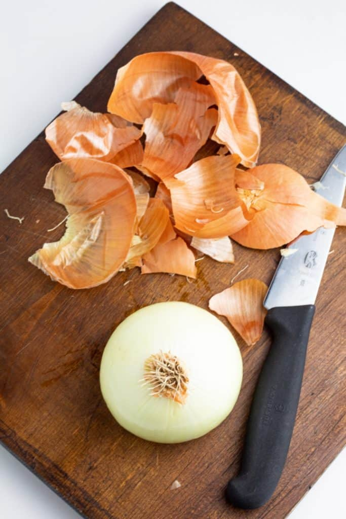 peeled onion on cutting board with knife