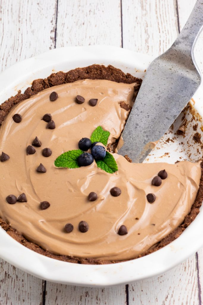 vegan chocolate pie in white pie dish with pie cutter