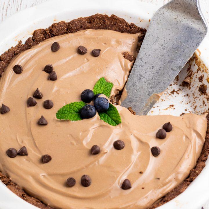vegan chocolate pie in white pie dish with pie cutter